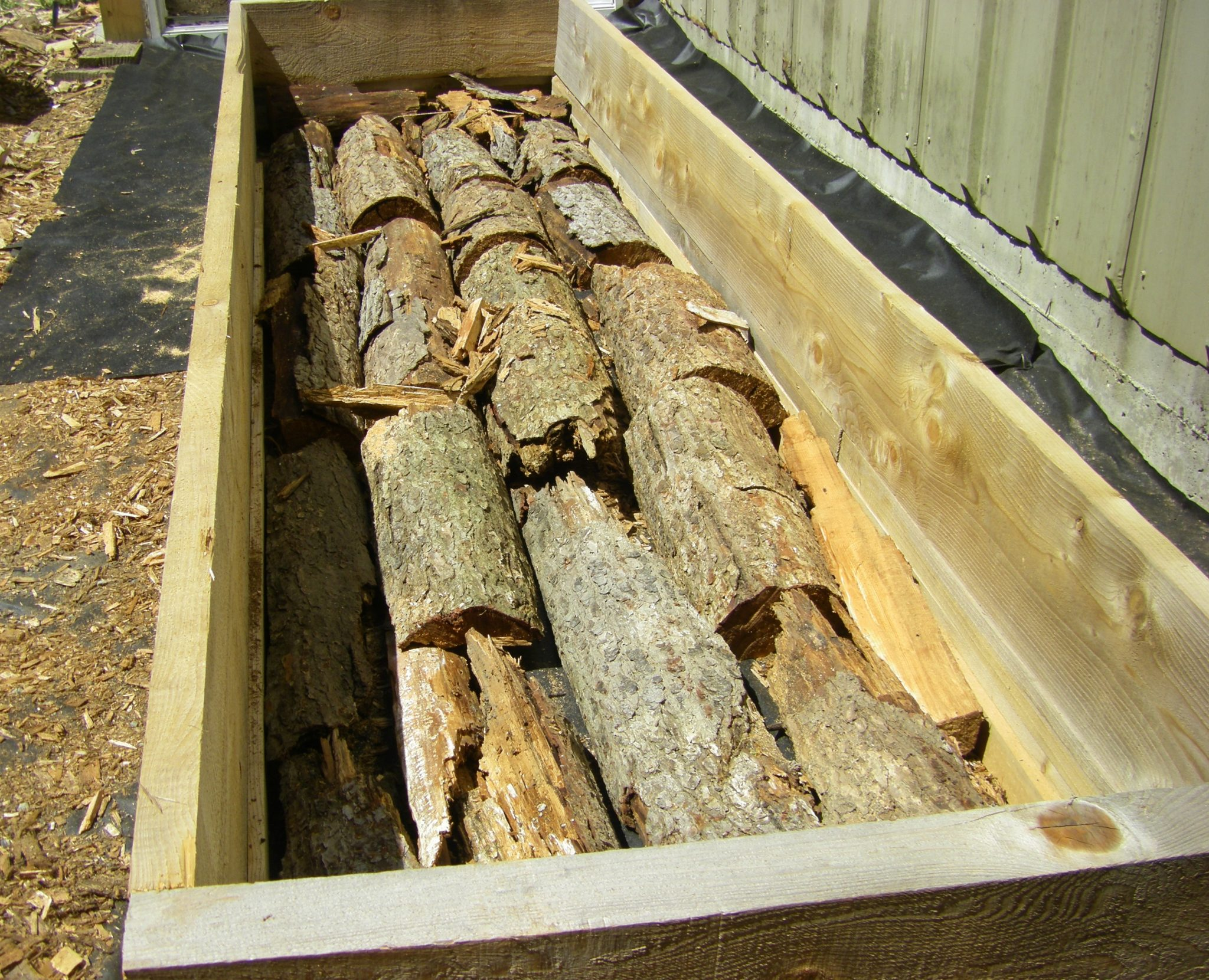 logs in bed to form hugelkultur